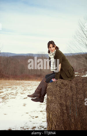 Woman looking away while sitting on hay bale against sky during winter - Stock Photo