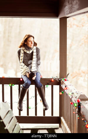 Woman looking away while sitting on railing - Stock Photo