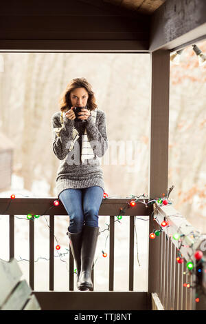 Portrait of woman enjoying drink while sitting on railing in porch - Stock Photo