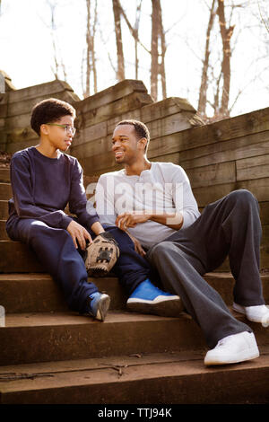 Father and son talking while sitting on steps - Stock Photo