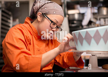 Woman decorating cake at store - Stock Photo
