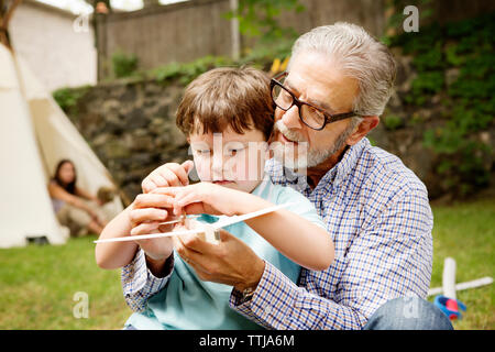 Boy playing with grandfather in lawn - Stock Photo