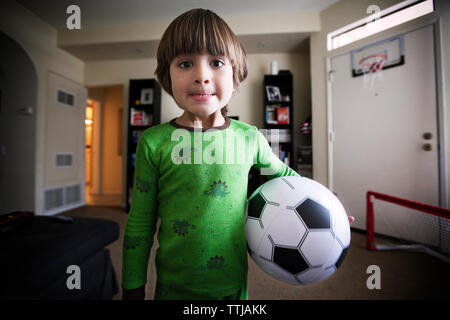 Portrait of boy holding soccer ball while standing at home - Stock Photo