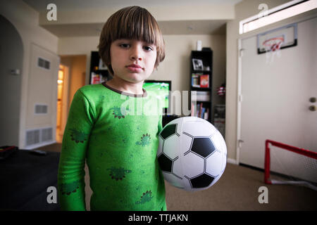 Boy holding soccer ball while standing at home - Stock Photo
