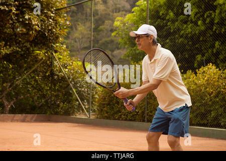 Senior man playing tennis at court - Stock Photo