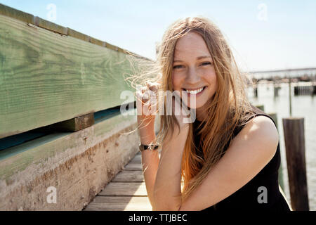 Portrait of smiling woman at pier - Stock Photo