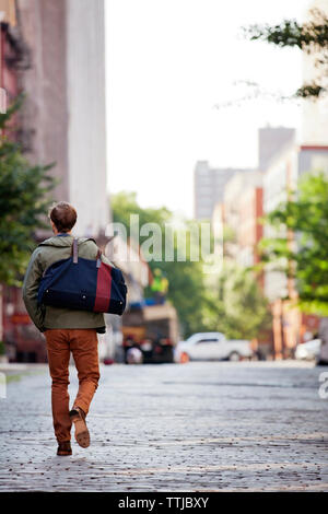 Rear view of man carrying bag while walking on street - Stock Photo