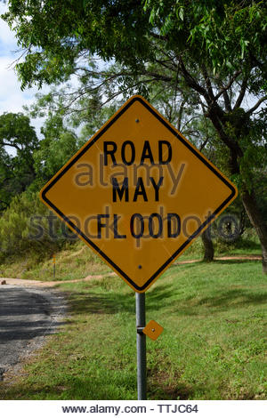 Road May Flood. United States Road Sign. Road May Flood Sign Low Water Crossing. Sandy Creek. Enchanted Rock. Highway Warning Sign Texas Hill Country - Stock Photo