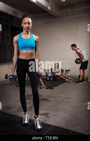 Woman holding dumbbells while standing with friends in background - Stock Photo