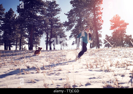 Playful woman with dog running on snow covered field - Stock Photo