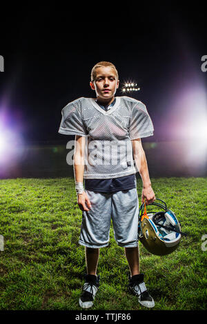 Portrait of football player holding helmet while standing on field - Stock Photo