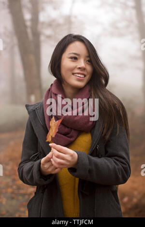 Woman with maple leaf looking away while standing in forest - Stock Photo