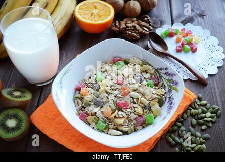 Muesli with candied fruits and nuts with a glass of milk on a dark wooden table. - Stock Photo