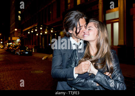 Romantic man kissing girlfriend while standing on city street at night - Stock Photo
