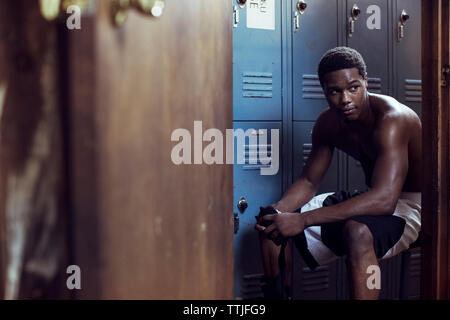 Boxer looking away while sitting in locker room - Stock Photo