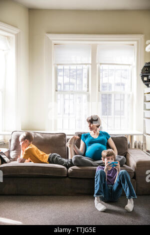 Pregnant woman with kids at home - Stock Photo