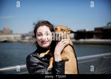 Portrait of happy woman with dog standing on footbridge against sky - Stock Photo