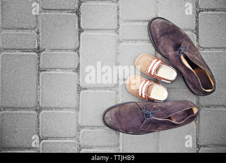 Father's shoes close to child's shoes on pavement background - Stock Photo