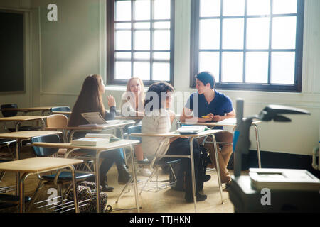 Friends sitting in classroom - Stock Photo