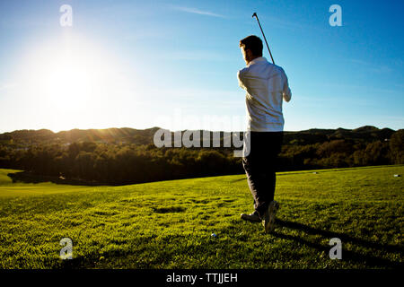 Rear view of man playing golf against clear sky - Stock Photo
