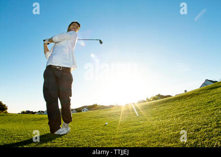 Man taking a shot of golf while standing against clear sky - Stock Photo
