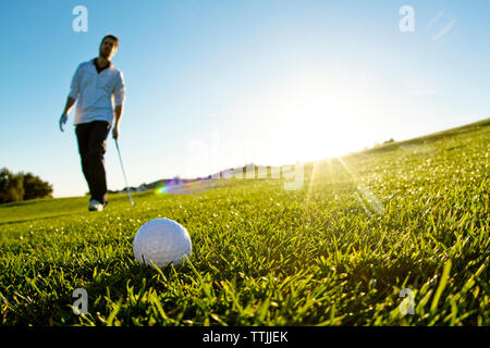 Man standing on golf field against clear sky - Stock Photo