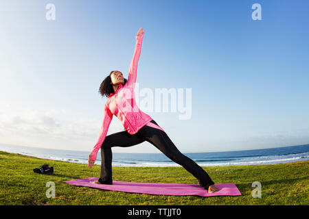 Woman practicing extended side angle pose on field against clear sky - Stock Photo