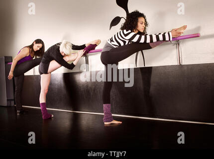 Ballet dancers stretching at studio - Stock Photo