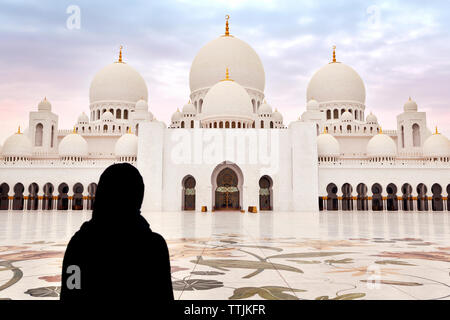 Rear view of woman standing against Sheikh Zayed Mosque - Stock Photo