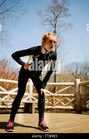 Exhausted woman with hand on hip looking away while standing in park - Stock Photo