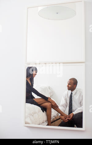 Man massaging woman's feet reflected in mirror - Stock Photo