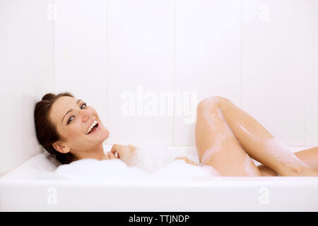 Portrait of smiling woman bathing - Stock Photo