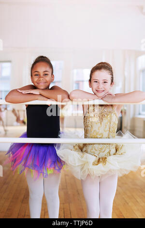 Portrait of smiling ballerinas leaning on rod in studio - Stock Photo