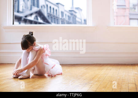 Girl wearing ballet shoes while sitting on hardwood floor in studio - Stock Photo