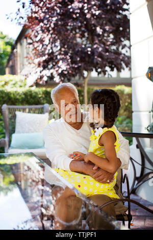 Girl sitting on grandfather's lap by table at home - Stock Photo