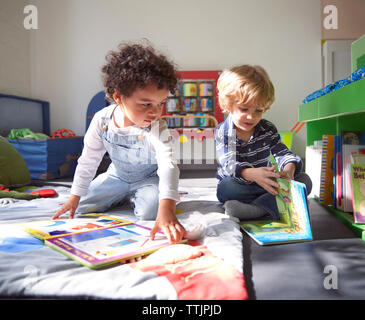 Children with picture books in kindergarten on sunny day - Stock Photo