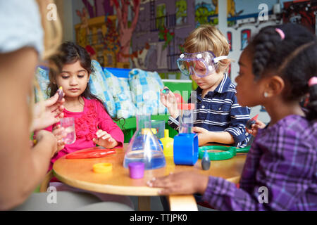 Children doing science experiment at table in preschool - Stock Photo