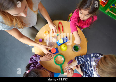 Overhead view of teacher assisting children in science experiment at preschool - Stock Photo