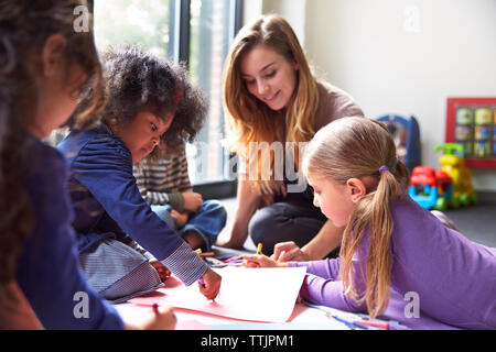 Teacher and students drawing on papers at child care - Stock Photo