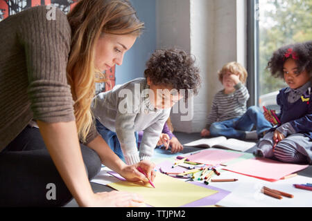 Teacher drawing with students on floor at preschool - Stock Photo
