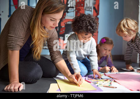 Teacher drawing on papers with students at preschool - Stock Photo