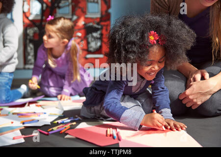 Cheerful girl drawing on paper while sitting by teacher at preschool - Stock Photo