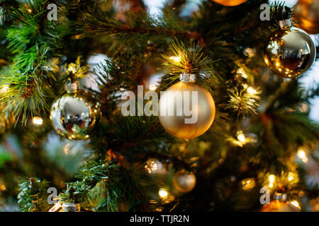 Close-up of ornaments and lights on Christmas tree - Stock Photo