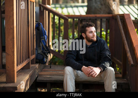Man looking away while sitting on steps - Stock Photo