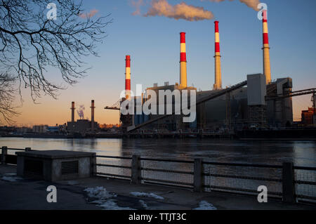 Smoke Stacks in factory against clear sky - Stock Photo