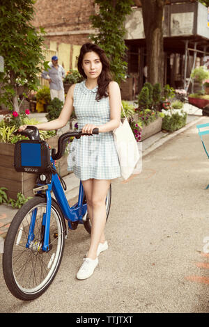Thoughtful woman with bicycle standing on city street - Stock Photo