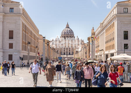 ROME, ITALY - APRIL 27, 2019: People walking along the famous via della Conciliazione with the Saint Peter Basilica in the distance. - Stock Photo