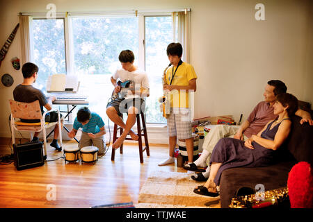 Parents looking at sons performing with music instruments in living room - Stock Photo