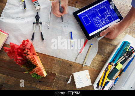 Cropped image of architect drawing blueprints while holding tablet computer at office - Stock Photo