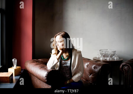 Thoughtful businesswoman sitting on armchair in office - Stock Photo